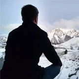a person sitting on a snowy mountain